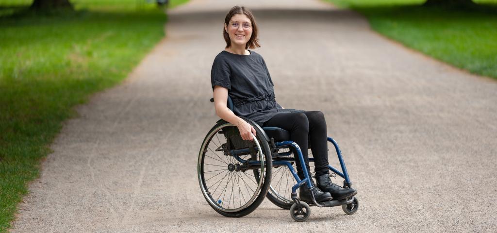 Bild von Mechthild Kreuser. Sie sitzt im Rollstuhl und hat ein schwarzes Kleid, schwarze Leggings und schwarze Schuhe. Sie steht auf einem Weg in einem Park.