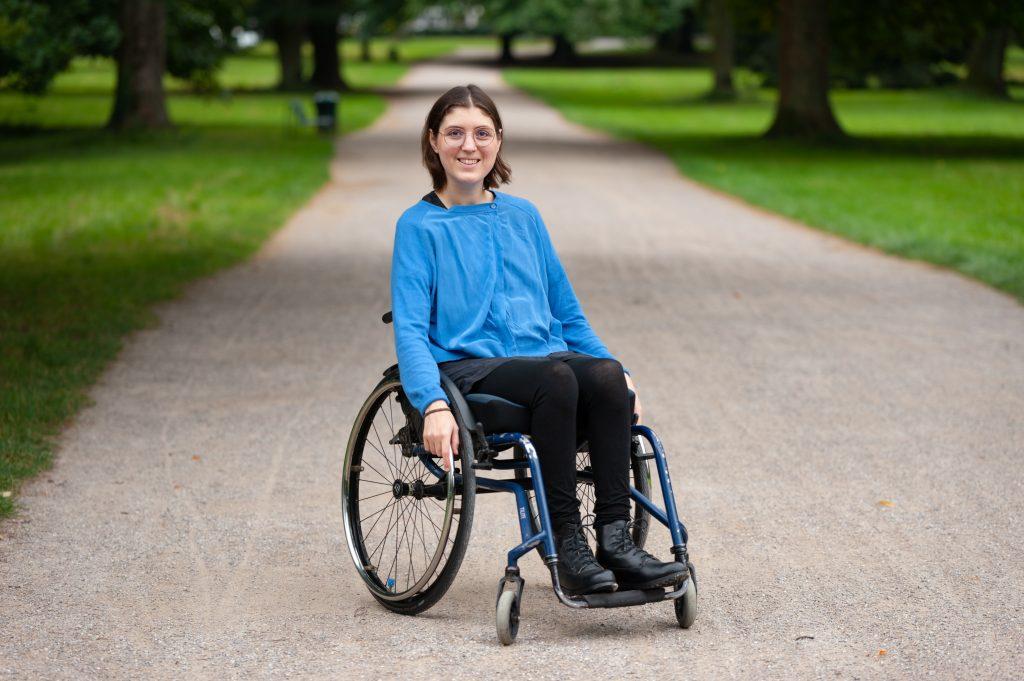 Mechthild sitzt im Rollstuhl und ihre Hände sind an den Greifreifen. Sie trägt eine blaue Jacke, ein schwarzes Kleid, eine schwarze Leggings und schwarze Schuhe. Sie steht auf einen Weg im Grünen.
